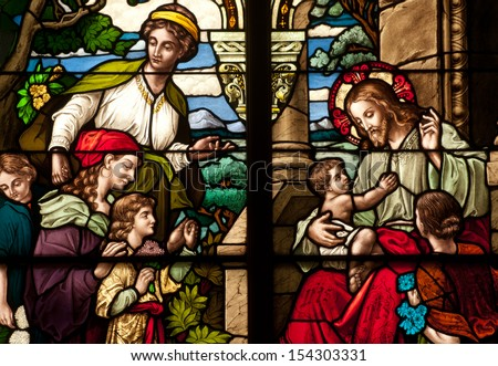 Stained glass window depicting the bible story of Jesus Christ with the little children