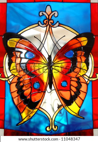 Stained glass window has brilliantly colored butterfly in orange, yellow and blue. - stock photo