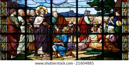 Stained glass window in St.Sulpice church (Fougeres, France), depicting a biblical scene:miracle of Jesus Christ by feeding a crowd of 5.000 with just five loaves of bread and two small fish. - stock photo