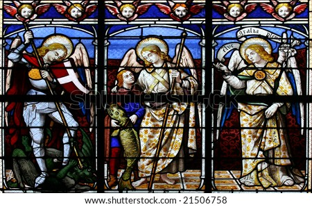 Stained glass window in St.Sulpice church (Fougeres, France), depicting (from left to right) The Archangels: Michael, Raphael and Gabriel. - stock photo