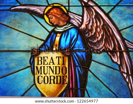 Stained glass window of angel holding shield with one of beatitudes in Latin, Blessed are the pure of heart