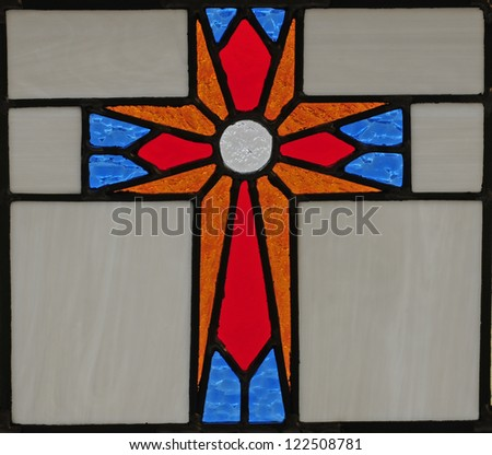 Stained glass window of red, blue and gold cross - stock photo