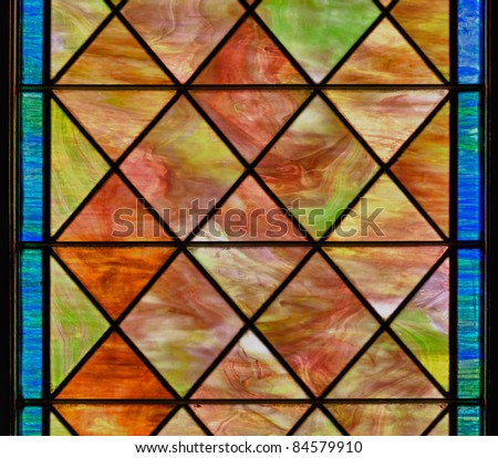 Stained glass window with diamond shapes and overall red brown color - stock photo