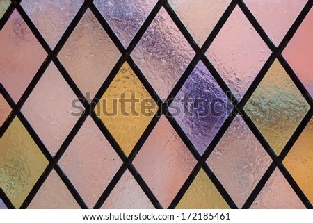 Stained glass with multi colored diamond pattern as background pink violet tone - stock photo