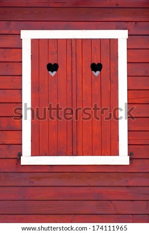 Stained wood window shutters closed, her heart symbol. - stock photo