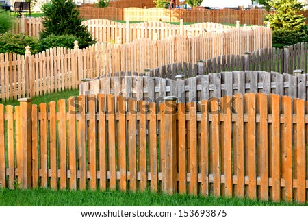 Staining wooden fence not easy job when you have lots of them, dream neighborhood for fence staining people - stock photo