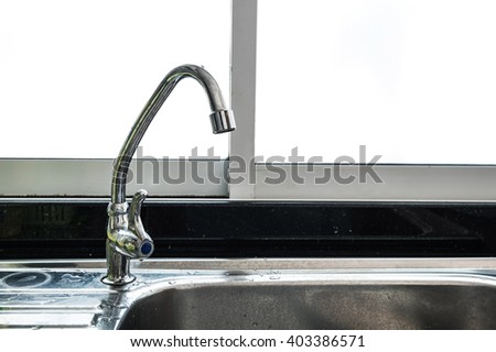 Stainless faucet and dirty sink in the kitchen - stock photo