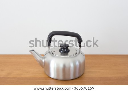 Stainless kettle on wood table with white background. - stock photo