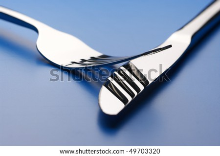 Stainless knife and fork on blue background.