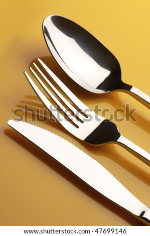 Stainless knife, fork and spoon on yellow background. - stock photo