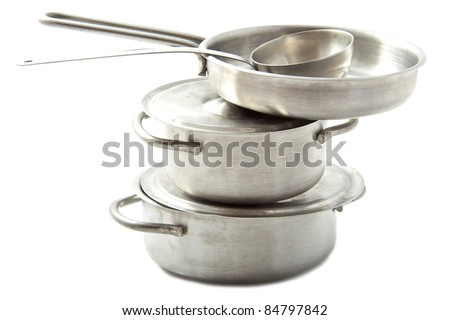 Stainless pots and pans on a pile - stock photo