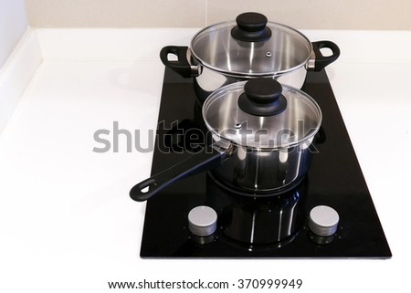 Stainless pots on electric cooktops - stock photo