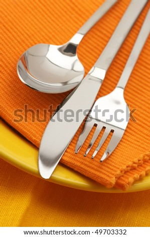 Stainless spoon, fork and knife on yellow plate with orange linen napkin. - stock photo