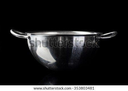 Stainless steel bowl on black background from side