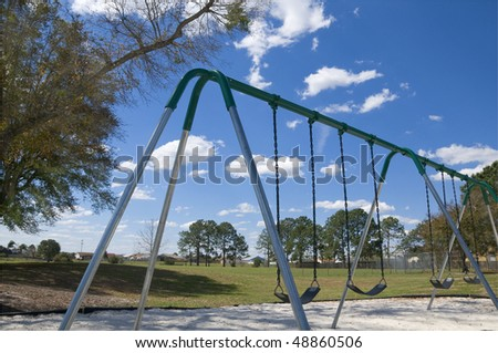Stainless steel childrens swing set with partly cloudy blue sky and southern oak tree near by - stock photo