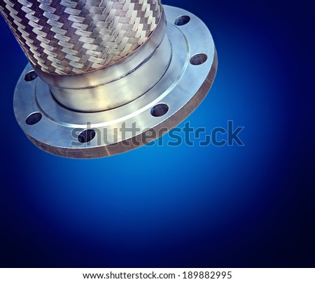 Stainless steel corrugated and braided metal hose with flange ending. Industrial background & space for text. - stock photo