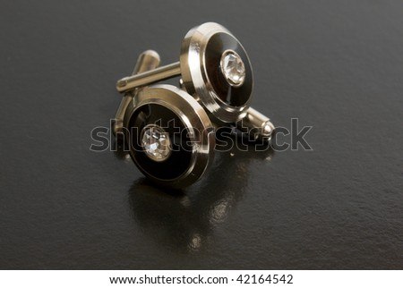 stainless steel cufflinks on the black background - stock photo