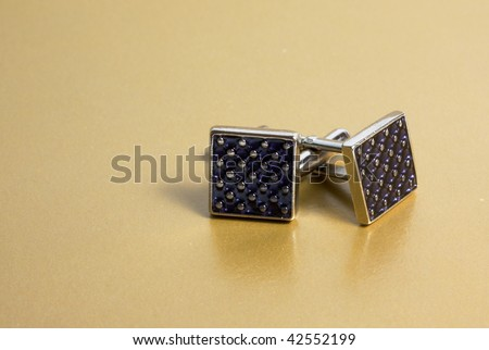 stainless steel cufflinks on the gold background - stock photo