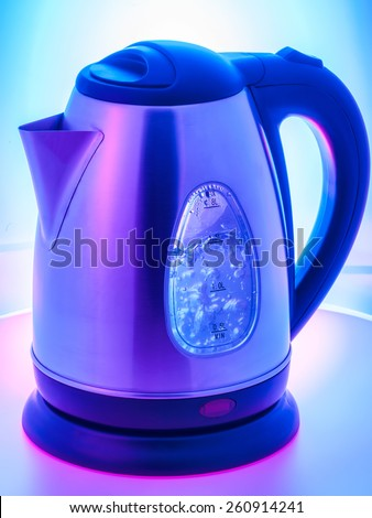 Stainless steel electric kettle with boiling water, abstract color background. - stock photo
