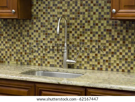 Stainless steel kitchen faucet and sink with mosaic  back splash - stock photo