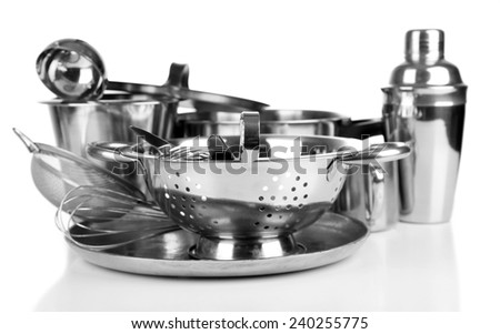 Stainless steel kitchenware on table, isolated on white - stock photo