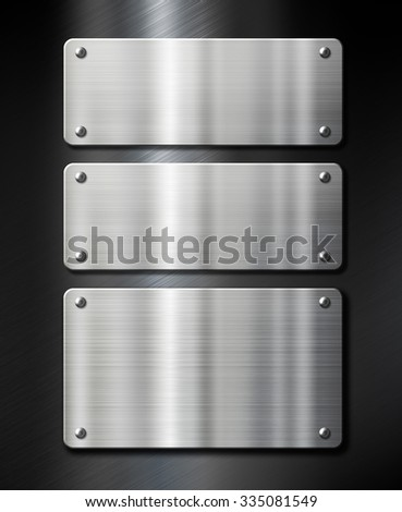 stainless steel metal plates on black brushed background - stock photo