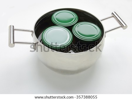 Stainless steel pot with three jars with green covers. Isolated on white background - stock photo
