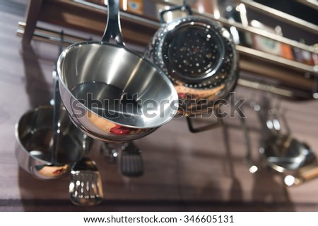 Stainless Steel Pots and Pans Hanging in Kitchen - stock photo