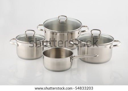 Stainless steel pots and pans on white background. - stock photo