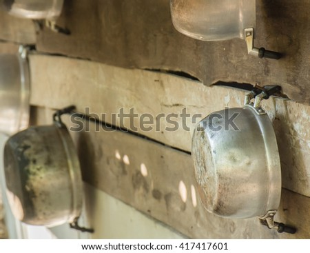 Stainless steel pots hanging on the wall in the kitchen of a house in rural Thailand. - stock photo