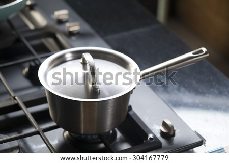 stainless steel saucepans on modern kitchen range - stock photo