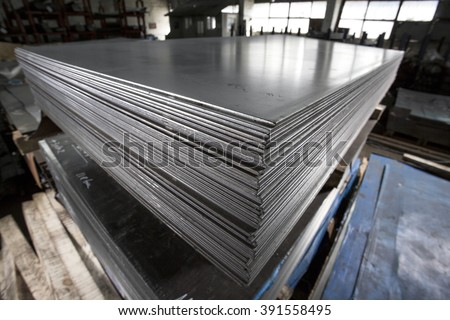 Stainless steel sheets deposited in stacks - stock photo