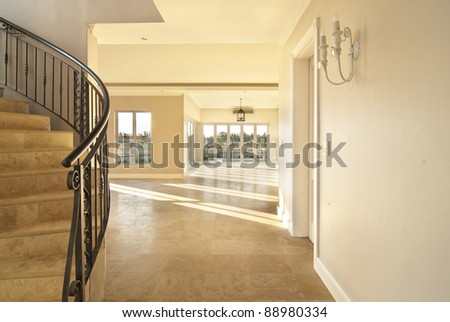 Staircase and empty lounge of a modern house. Everything is tiles with sunlight coming through the windows - stock photo
