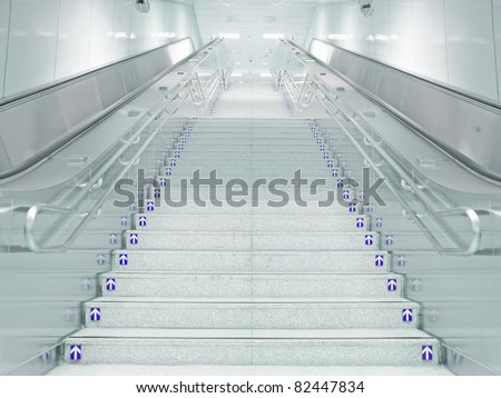 Staircase and escalator in underground passage - stock photo