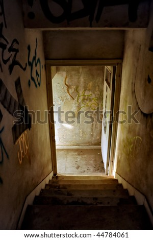 Staircase and exit door of an abandoned house. - stock photo