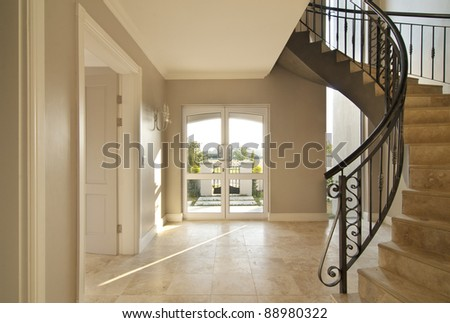 Staircase and front door area of a modern house. Staircase is framed on the right and the outside is visible through the front door. Both the staircase and floor is tiled
