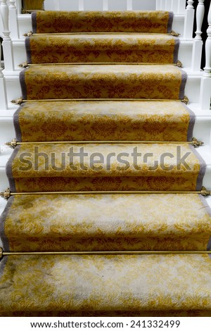 Staircase covered with luxury gold carpet - stock photo