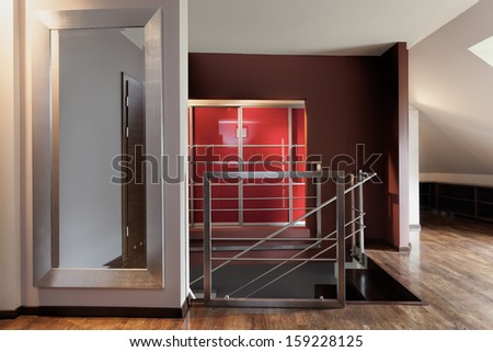 Staircase, huge mirror on the corridor of a modern house - stock photo