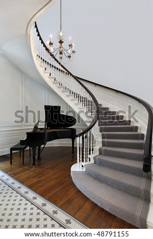 Staircase in front entry with cove for piano - stock photo