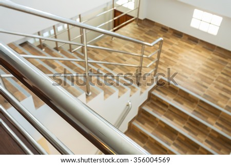 staircase in residential house with stainless steel banister - stock photo