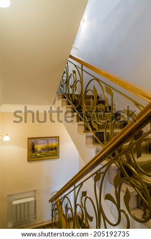 Staircase in the house with wrought iron fence and carpet - stock photo