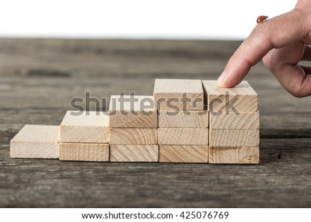 Staircase made of wooden pegs with male finger on top with a ladybug on it representing a way to success. - stock photo