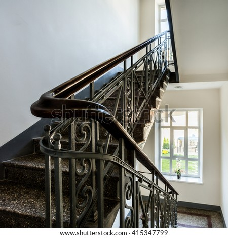 Staircase with old, decorative railing and white walls - stock photo