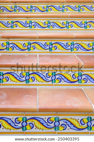 Staircase with patterned ceramic tiles and terracotta. - stock photo