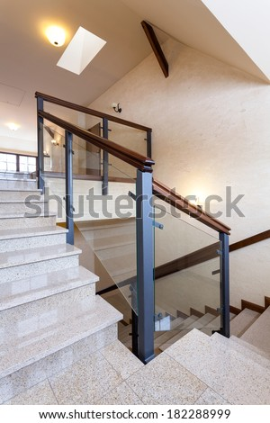 Staircase with stone steps and glass banister - stock photo