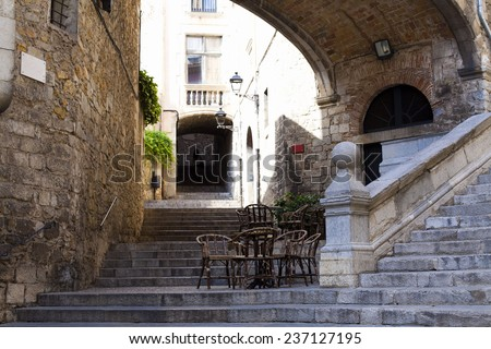 Stairs and cafe on the background of the stone walls in the square of St. Dominic in Girona, Spain.