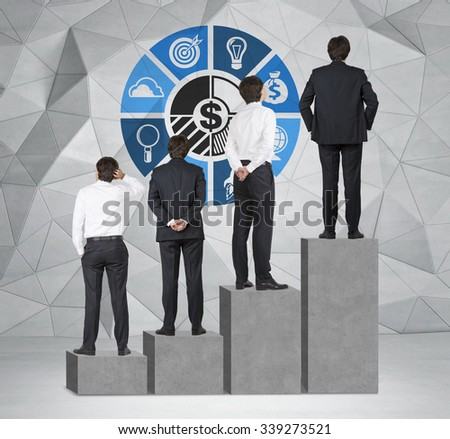 Stairs as a huge concrete bar chart are in the room with concrete floor and contemporary wall. Businessmen are standing on each step as a concept of corporate ladder. Business diagram on the wall - stock photo