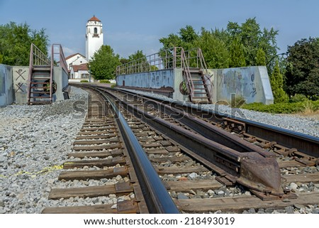 Stairs bridge and train tracks and depot with graffiti - stock photo
