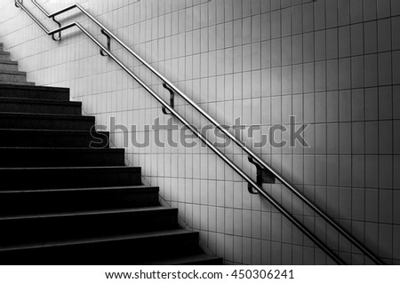 Stairs in stone and a metal rail in black end white. - stock photo