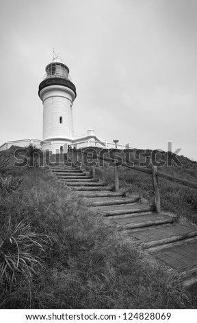 Stairs lead up to a lighthouse on top of a hill. - stock photo
